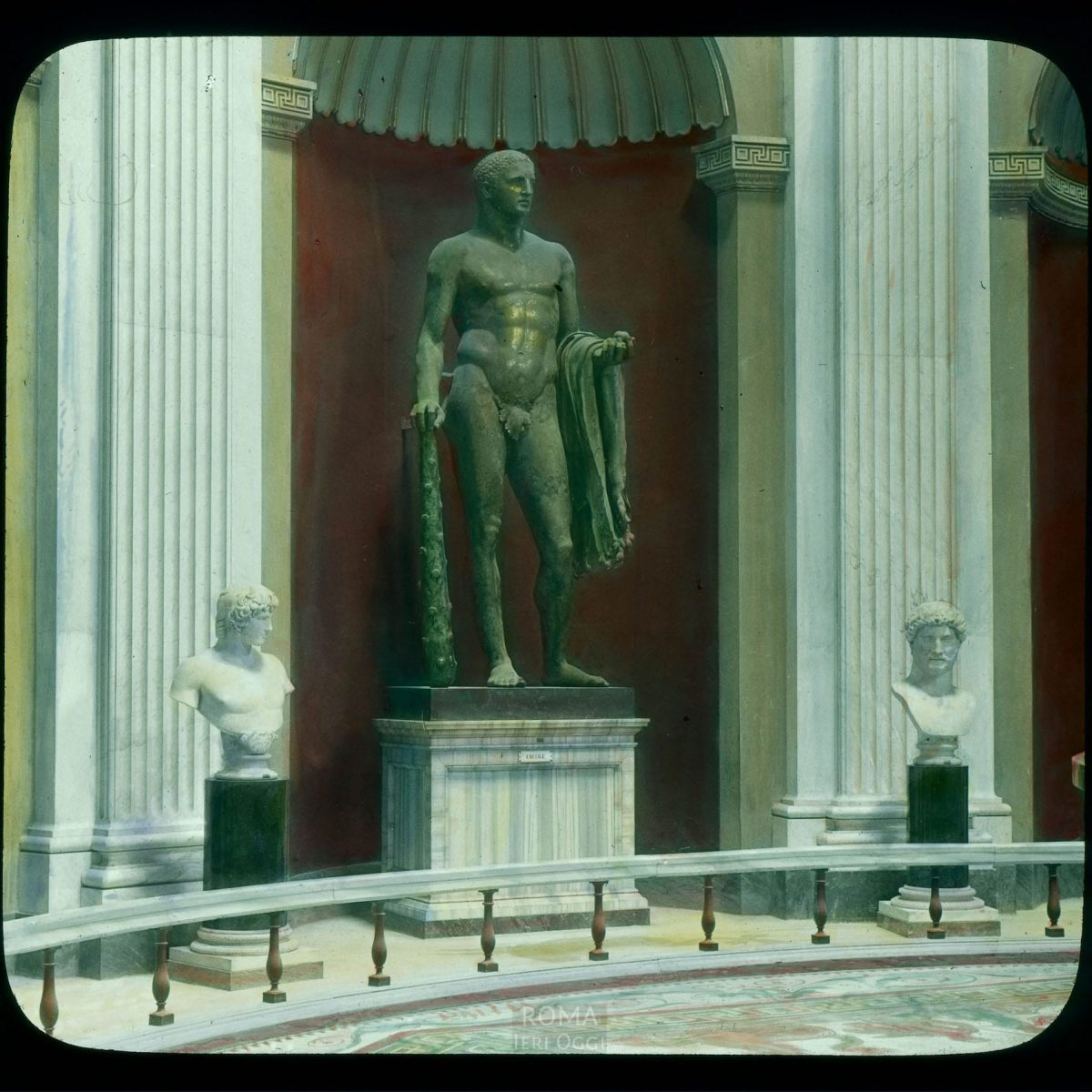 Vatican City. Vatican Museum, Museo Pio-Clementino: Hercules of the Theatre of Pompey, on display with two busts View in tinted lantern slide, ca. 1919-1938. The gilded bronze statue dates from the early 3rd century B.C.E.